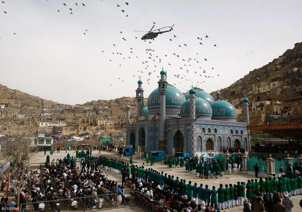 Afgán rendőrségi helikopter vigyázza a közös imát Kabulban, az afgán újév első napján. A perzsa naptár Mohammed próféta medinai zarándokútjától számolja a napokat, így ott idén még csak 1391.-et írunk. (Március 20.)