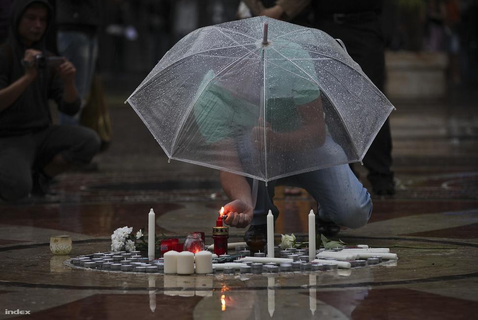 Bándy Kata emlékére gyújt mécsest az esőben egy megemlékező a Szent István Bazilika előtt július 21-én. Bándy Kata július 8-án, vasárnap hajnalban tűnt el, miután egy szórakozóhelyről hazaindult. Holttestét július 11-én, szerdán találták meg otthonától fél kilométerre. Feltételezett gyilkosát egy héttel később fogták el, P. László azóta beismerő vallomást tett. A rendőrség ennek ellenére folytatta a nyomozást.