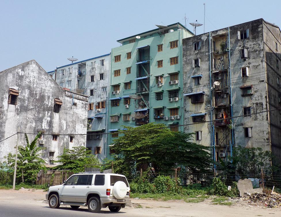 Yangoni városkép. A házakat a szubtrópusi éghajlaton jó esztétikai állapotban tartani szinte folyamatos kiadást jelentene, ezért sok helyen meg se próbálják. A monszunidőszak hatalmas esőzései eláztatnak mindent, az épületeket sem kímélik. Az előtérben egy jó állapotú Isuzu Bighorn, az Ázsiában igen népszerű Isuzu Trooper egyik változata.