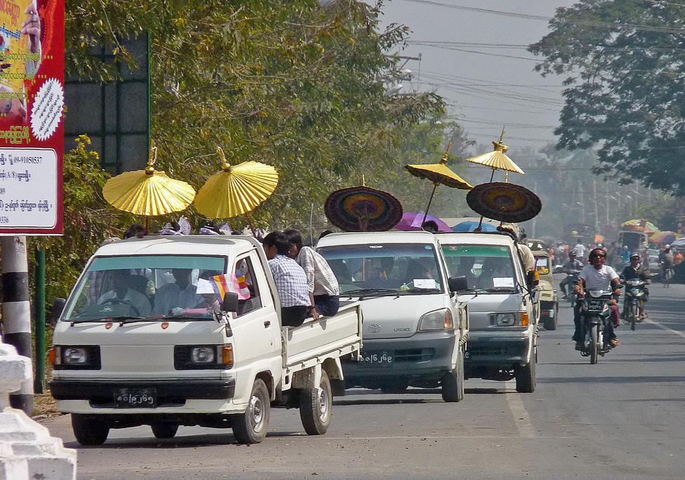 Buli van: a mulatság helyszínére tart Mandalay-ben a motorizált esküvői menet. A násznép ernyőkkel védekezik az erős napsugárzás ellen, amit némileg tompít a várost folyamatosan ellepő szmog, ami ellen viszont nincs védelem. A nap 24 órájában nyüzsgő, zsúfolt belvárosban igen élénk a forgalom, az öreg és elhasznált, katalizátort sohasem látott motorok ontják magukból a kipufogógázokat.