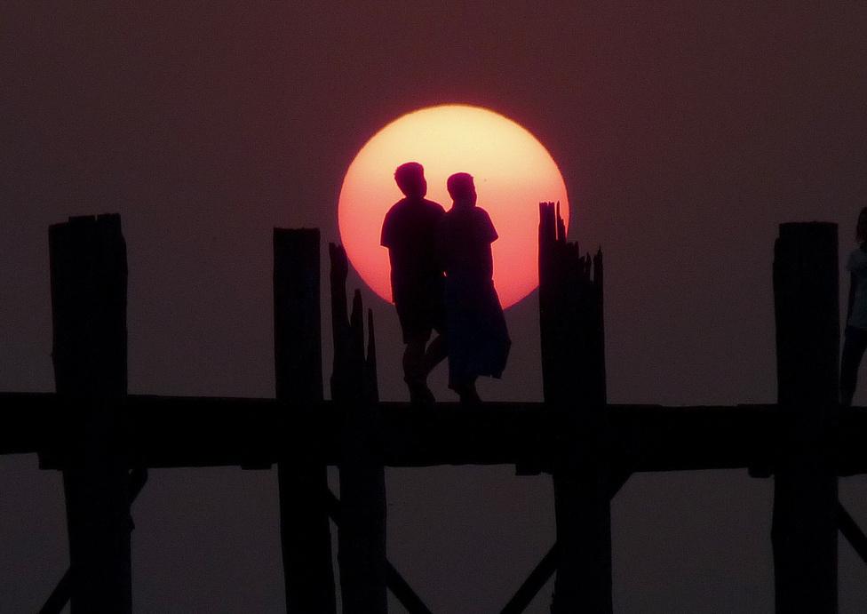 """A közlekedés alapformája: a gyaloglás. Másként nem is lehet áthaladni a világ alighanem leghíresebb tikfa hídján, a Taungthaman-tavon átvezető, 1200 méter hosszú U Beinen. A hidat az 1800-as évek közepén építették, hogy lerövidítsék az utat az egykori főváros, Amarapura és Mandalay között, illetve hogy egyszerűbbé tegyék a tó környékén élők közlekedését. Az U Bien ma az egyik leglátogatottabb burmai turistacélpont, miközben hibátlanul teljesíti eredeti, """"közszolgálati"""" szerepét is."""