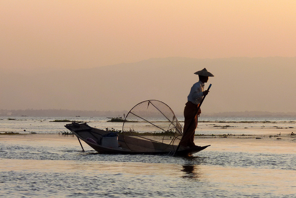 Halászat hagyományos módszerekkel az Inle-tavon. A 880 méter magasan fekvő hegyvidéki tó Burma egyik legizgalmasabb látnivalója. Mintegy százezer ember él a partvidékén és magán a vízen, ahol egész falvakat találni, templomokkal, iskolákkal, üzletekkel. A tavon élők a zöldséget a vízen úszó növényszigeteken termelik meg.