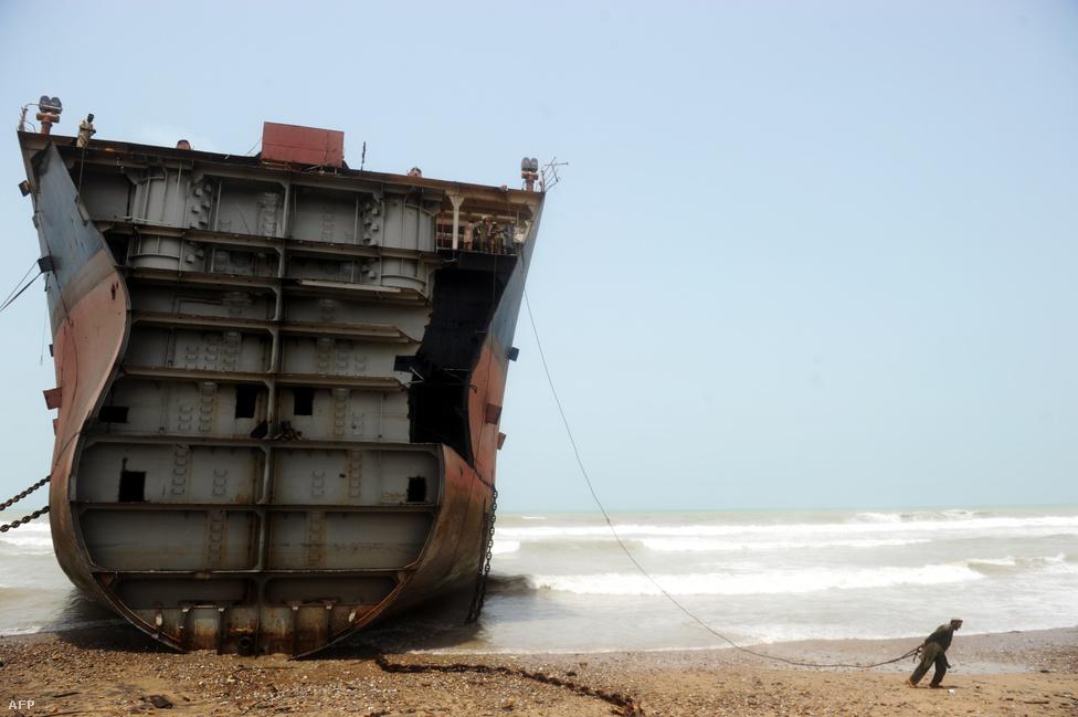 Hajóbontó munkás készül teherautójához láncolni egy partra vetett tankerhajó borításának egy darabját, hogy azt a jármű erejével le tudja választani a hajótestről a pakisztáni Geddani város tengerparjtán.