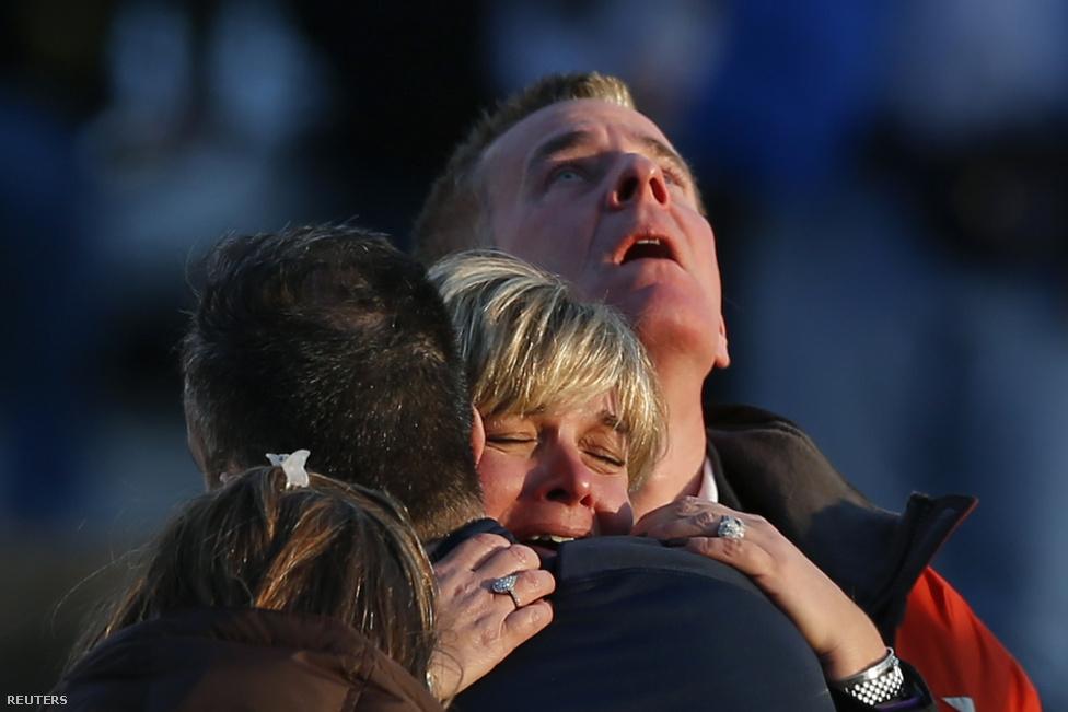 Gyászoló családtagok a newtown-i Sandy Hook általános iskolában történt lövöldözés után. December 14-én egy 22 éves fegyveres férfi 28 embert, köztük 20 kisgyereket ölt meg az intézményben.