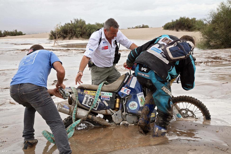 Etienne Lavigne, a Dakar főrendezője (középen) segít a Yamaha francia motorásanak, Hervé Thierrynek kitolni motorját a sárfolyamból.