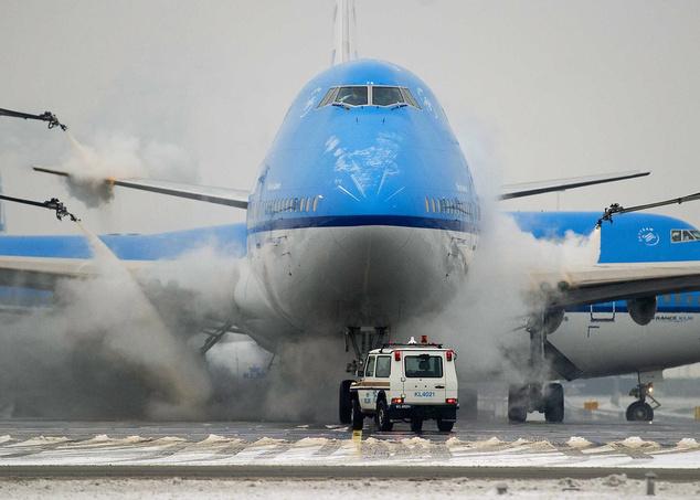 A KLM holland légitársaság egyik személyszállító repülőgépét jégtelenítik felszállás előtt az amszterdami Schiphol repülőtéren