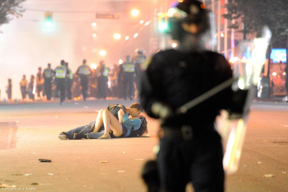 2011. A Vancouver Canucks kikapott a Stanley-kupa döntőjében, mire a város utcáit ellepték a dühödt szurkolók. Bár a felvételen úgy tűnik, hogy egy pár a rohamrendőrök között, a földön fekve csókolózik, valójában a fiú épp sokkos állapotban került barátnőjét próbálja nyugtatni.