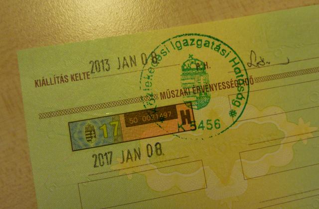 A műszaki vizsga érvényességét jelölő oldal a forgalmi engedélyben. A címer melletti szám jelzi a lejárat évszámát, alatta pedig leolvasható a teljes lejárati dátum.
