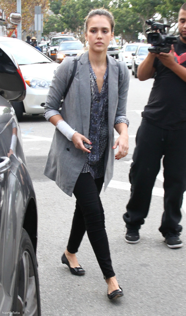 Jessica Alba fekete nadrággal és papucs cipővel párosította a trendi kabátot.