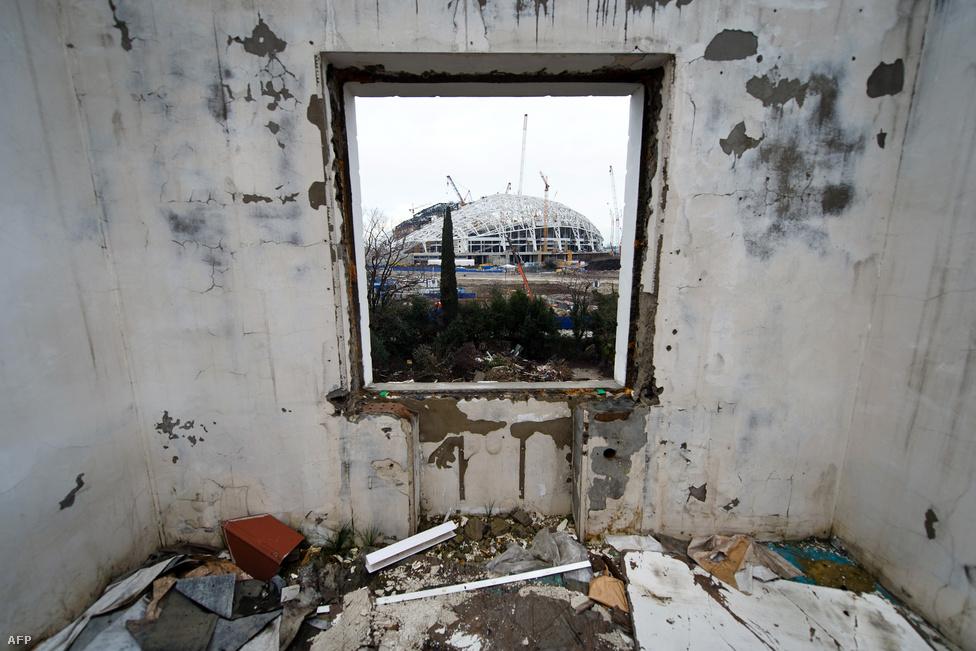 Az olimpiai stadion egy elhagyott ház ablakából.                         A kogyepsztaiaknál is rosszabbul járt az a Human Rights Watch becslései szerint 1500 család, akiknek szimplán lerombolták az otthonát. Sokuk még kompenzációt sem kapott - a hatóságok helyzetét könnyítette, hogy a posztszovjet zűrzavarban a tulajdoni viszonyok változásait hézagosan dokumentálták. Pedig az építkezések miatt a város egyik negyedét, a nevében békés Mirnijt gyakorlatilag porig rombolták. A negyedben mintegy harminc ház maradt, a többit eltakarították az autópályák és az olimpiai stadion útjából.