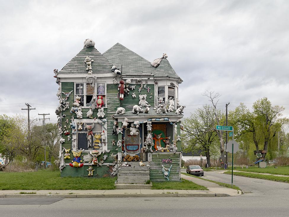 """Animal House, Heidelberg telep, Detroit, 2010 A Heidelberg telep egy helyi művészeti kezdeményezés. """"Művészet, Energia, Közösség"""", írja Jordano a szabadtéri kiállításként is funkcionáló városi közösségről. Az eastside-i telep alapítója és művészeti vezetője, Tyree Guyton eldobott használati tárgyakat felhasználva alakított színkavalkáddá egy kétháztömbyi területet. Az idén már 26 éves projekt világszerte elismert demonstrációja annak, hogy a kreativitás ereje hogyan alakíthat át életeket."""