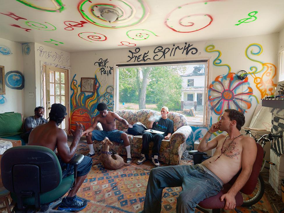 Beezy és a haverok, Goldengate Street, Detroit, 2012 Beezy 2011 novemberében költözött be a Goldengat utcai lakatlan házba. Azóta kicserélte az ajtókat, az ablakokat, újrafalazott. Az építőanyagokat adományként kapta. Barátai a szomszédos házakat újították fel ugyanígy.  Együtt kertészkednek, csirkéket nevelnek, közösen főznek és mindenen osztozkodnak. Erőfeszítéseik a város egyik legnehezebb sorsú negyedében jelentenek reményt, írja Jordano.