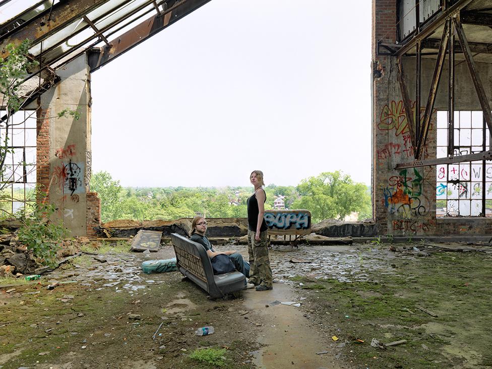 Kat és Rick, városi felfedezők a Packard Autógyárban, Detroit, 2010 Kat és Rick lelkes graffitizők, akik gyakran járnak a Packard autógyár 350000 négyzetméteres csarnokába, a város graffitiseinek szimbolikus otthonába. A gyár egyik falára maga Banksy fújt egy festményt, de egy magukat Megőrzőknek nevező csoport az egész téglafalat elbonotta. A gyár tulajdonosa pert indított a több tízezer dolláros értékűre becsült festményért, de a Megőrzők nem hajlandók átadni.
