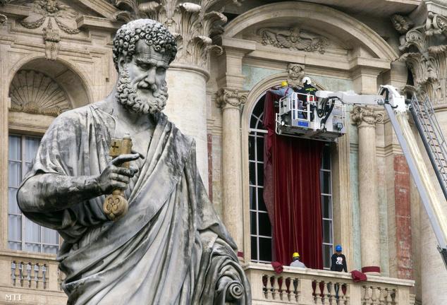 Burgundi bordó függönyt akasztanak fel a vatikáni Szent Péter-bazilika középső erkélyének ajtaja elé 2013. március 11-én a bíborosi konklávé kezdete előtti napon. Itt a balkonon jelenik majd meg először az ünneplő tömeg előtt az újonnan megválasztott pápa.