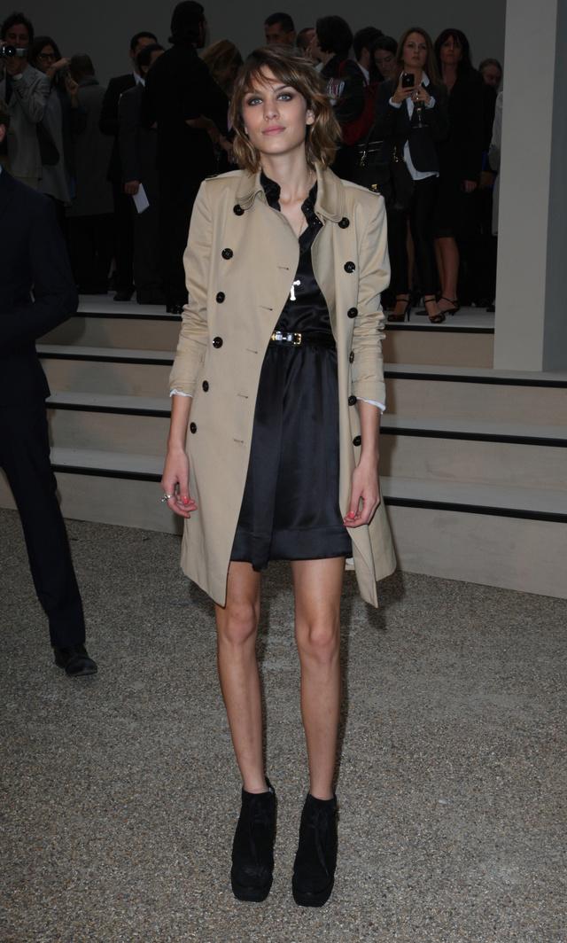 Alexa Chung ballonkabátban, rövid selyemruhában és feltűnő cipőben a Burberry bemutatóján.