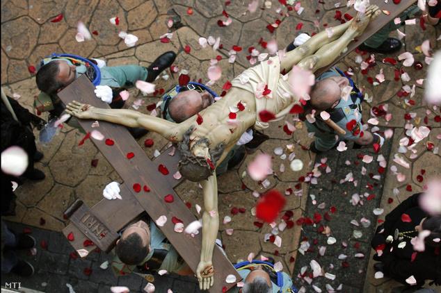 Hívők virágszirmot szórnak a feszületre amelyet spanyol légionárius lovagok visznek a virágvasárnapi körmeneten az észak-spanyolországi Ovideóban