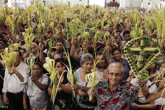 Katolikus hívők pálmaágakat visznek a virágvasárnapi körmeneten a salvadori fővárosban, San Salvadorban