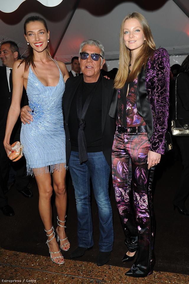Roberto Cavalli május 22-én, pénteken rendezett bulit Cannes-ban. A Getty csak anynit írt a képhez, hogy a fotón Cavalli látható két vendéggel, de mi felismertük Mihalik Enikőt, aki csillogó, lila mintás kosztümben érkezett a partiba.
