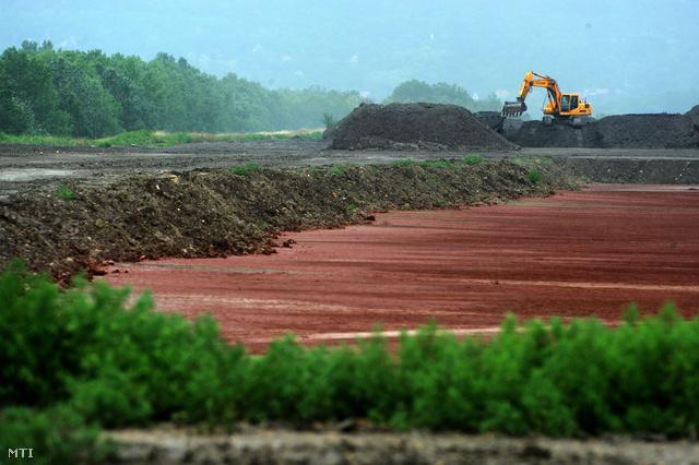 A már feltöltött területen növények telepedtek meg 2012-ben. A háttérben a Tatai Környezetvédelmi Zrt. (TKV) munkagépe mesterséges talajjal fedi be a volt Almásfüzitői Timföldgyár vörösiszap-tározóját.