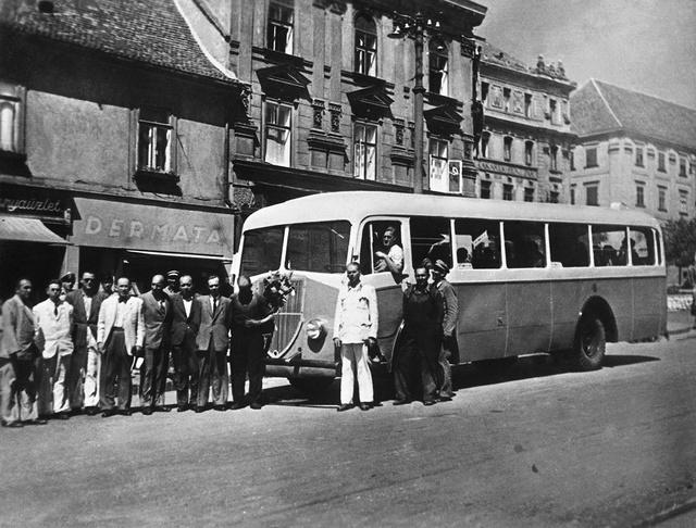 Pécs főterén a villamos elött látható egy Büssing. Városi járat lévén pótkereket nem vittek, azt a szervizkocsi szállította