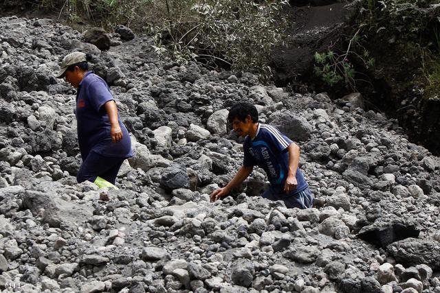 A tűzhányó kilövellte kövek között mennek férfiak az ecuadori Tungurahua tartományban fekvő Juive Grande közelében