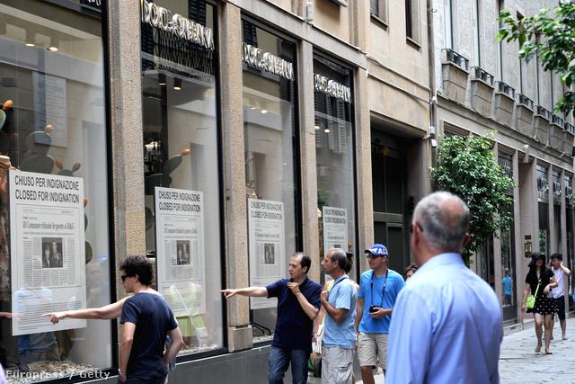 Járókelők nézik a tervezőpárosról szóló cikket az üzlet kirakatában.