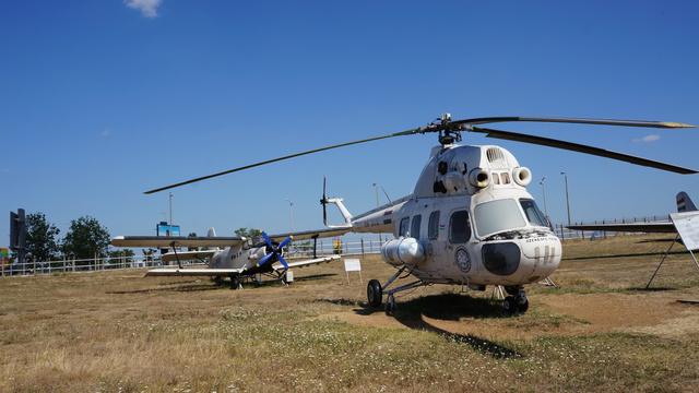 """Mi–2 (HA-BCB). A repülős szlengben """"Repülő csirkecombnak"""" is nevezett Mi–2-es helikoptert 1980 januárjától az Országos Mentőszolgálat használta mentő- és betegszállítóként. 1994-ig Székesfehérváron állomásozott. Ez év augusztus 14-én Ferihegyre repült nagyjavításra, de erre végül nem jutott pénz, ezért 1998-ban 2841 repült órával és 7732 felszállásszámmal selejtezték. Az Emlékparkba 1999. április 27-én vontatták át. (forrás: Wikipédia)"""