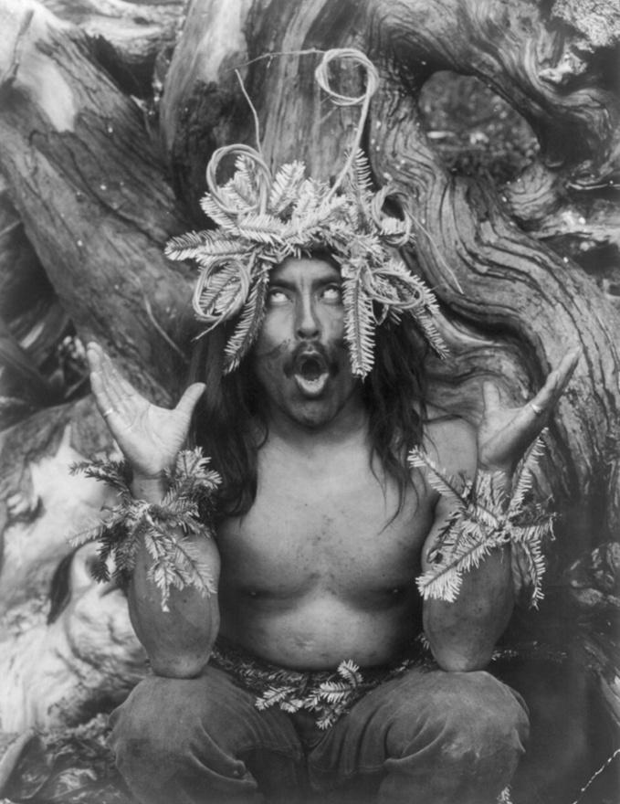 Hamatsza sámán guggol egy fa előtt, miután visszatért egy többnapos beavatási szertartásról (1914 körül)