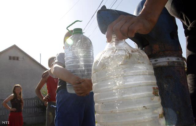Emberek vizet vesznek egy leszűkített közkútból Ózd sajóvárkonyi településrészén 2013. augusztus 4-én.