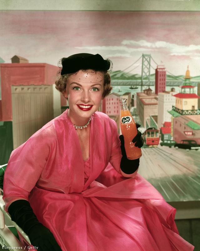 Trudy Wroe modell egy rózsaszín ruhában és fekete kalapban illetve kesztyűben reklámozott szénsavmentes narancslevet 1950-ben.