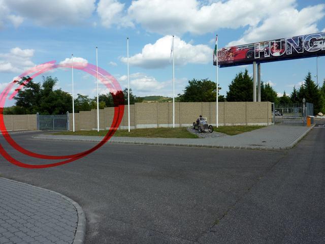 A látogatóké ez a kapu, ezen keresztül jutnak a lenti parkolóba, ahol az OKF-bemutató zajlik és ott lehet kipróbálni a füstalagutat is. A belépés és parkolás ingyenes, a paddock alig pár perc séta