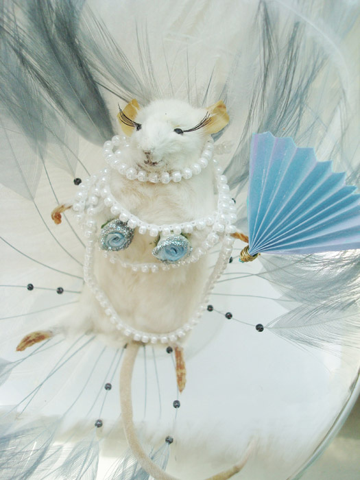 Kitömött fehér egér gyöngysorral és legyezővel.