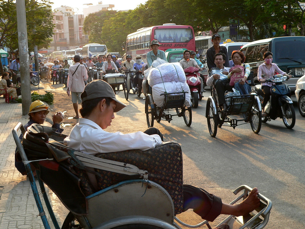 Mindenből egy kicsi, ami összesen már elég sok: ezen a saigoni fotón együtt láthatjuk szinte az összes jellegzetes vietnami járművet. A korábban fontos taxi-szerepet játszó riksák mára háttérbe szorultak, a riksások leginkább a turisták megvágásából, és árufuvarozásból próbálnak megélni. Bicikliből is egyre kevesebb gurul, és minden biciklis álma egy robogó, amivel viszont dugig vannak az utak. Nem csoda, hogy Vietnam az egyik legnagyobb robogó-gyártó ország Ázsiában. Magánautót egyelőre még kevesen engedhetnek meg maguknak, de amint valaki megteheti, azonnal vásárol egyet, és nő az állami, céges gépkocsik száma is. Hiába figyelmeztetnek a közlekedési szakemberek, hogy a nagyvárosi utak be fognak dugulni, ha sokan ülnek át kétkerekű járművekről a négykerekűekbe, a folyamat feltartóztathatatlanul halad előre.