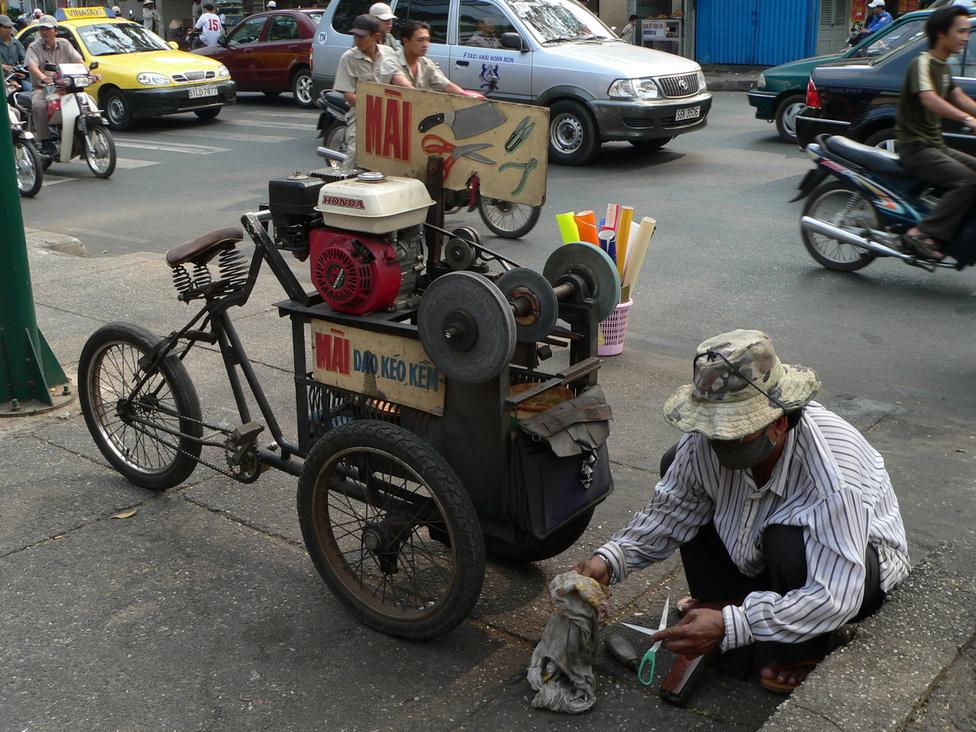 Nemcsak a divatozást, de a munkát is szolgálják a háromkerekű járgányok: ezzel a triciklivel például a vándorköszörűs járja Saigon negyedeit, és a hatalmas városban mindig talál éleznivalót. Direkthajtás és barkácsolt V-fék: a mobilizált köszörűvel kemény sport a közlekedés a felgyorsult forgalomban.