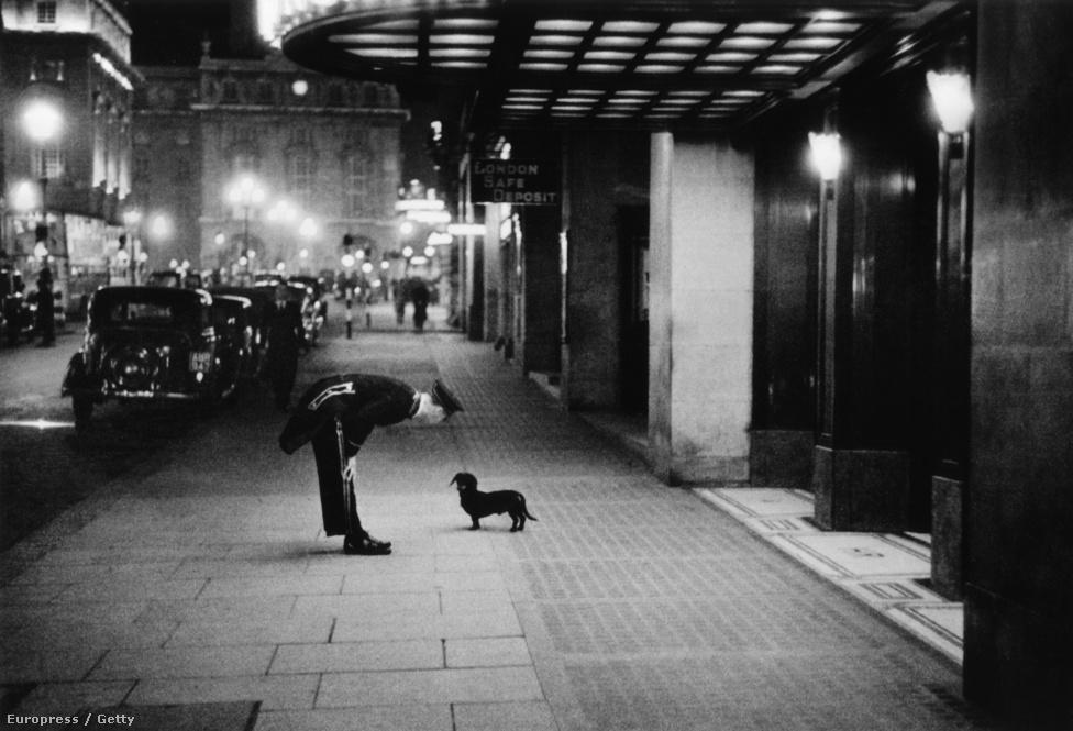 1938. Londíner és tacskó beszélgetnek a Piccadilly Circus egyik szállodája előtt.
