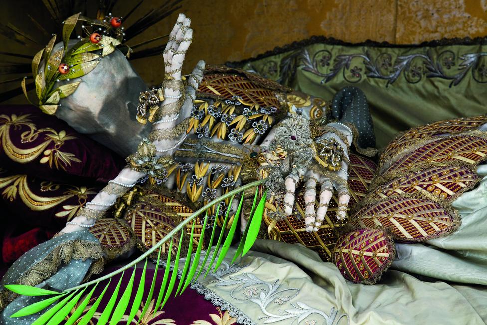 Stams, Ausztria. A díszítést legtöbbször apácák végezték, olykor szerzetesek. A folyamat soká tartott. Először is bevonták a csontokat enyvvel, hogy megerősítsék őket, aztán könnyű vászonba tekerték, hogy védjék a káros hatásoktól. Néha a csontvázak nem maradtak fenn teljes egészében, ilyenkor mesterséges csontokkal pótolták, ami hiányzott, vagy túlságosan megrongálódott. Az arc elé emelt kéz a szerénység gesztusa.