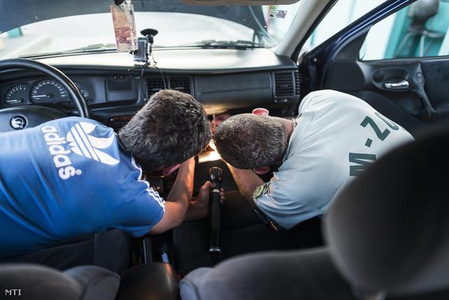 A Nemzeti Adó- és Vámhivatal vám- és pénzügyőr munkatársa egy autót vizsgál át a tiszabecsi határátkelőhelyen a magyar–ukrán határon 2013. május 10-én.