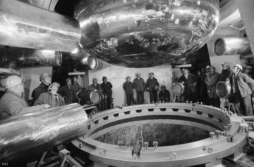 1980. október 19. A reaktortérbe érkezik a 230 tonna súlyú, 12 méter hosszú acéltartály a + 6 méteres szintre, ahol a reaktorcsonkokat fogják összehegeszteni a főkeringetőköri csővezetékkel a Paksi Atomerőmű reaktorépületében.