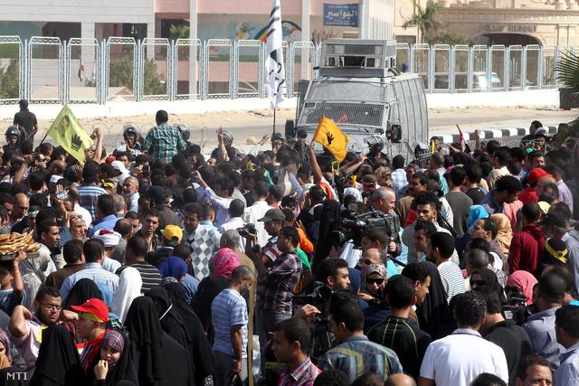 A hivatalából a hadsereg által eltávolított Mohamed Murszi volt egyiptomi államfő támogatói tüntetnek a kairói rendőrakadémia elkerített épülete előtt Murszi bírósági tárgyalásának helyszínén.