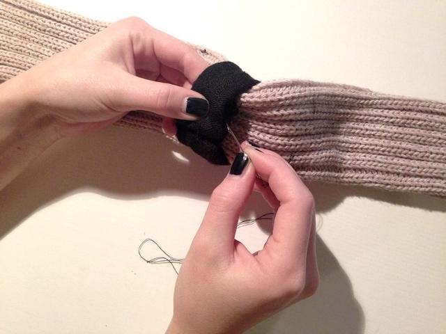 A díszek felvarrása után rögzítse a lábszárvédő közepére a sáldarabot, ezt is erősen varrja oda.