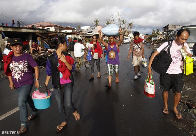 Egy zsák rizst visz a fején egy férfi a tájfun által letarolt Tacloban város utcáján