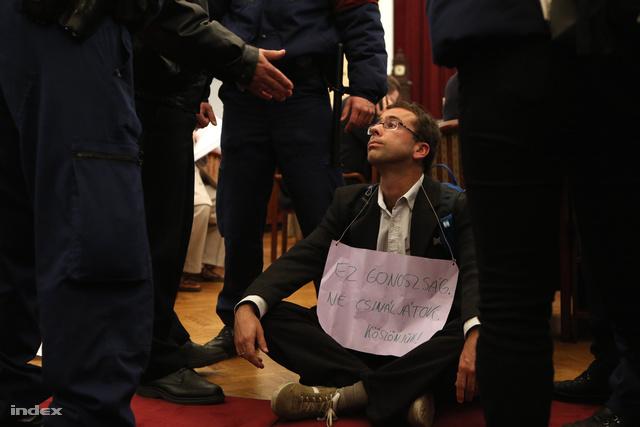 Az aktivisták továbbra sem mozdultak és a kórus is tovább zengett. A terembe időközben beérkező készenléti rendőrök elkezdték egyenként kivinni az egyesület tagjait.