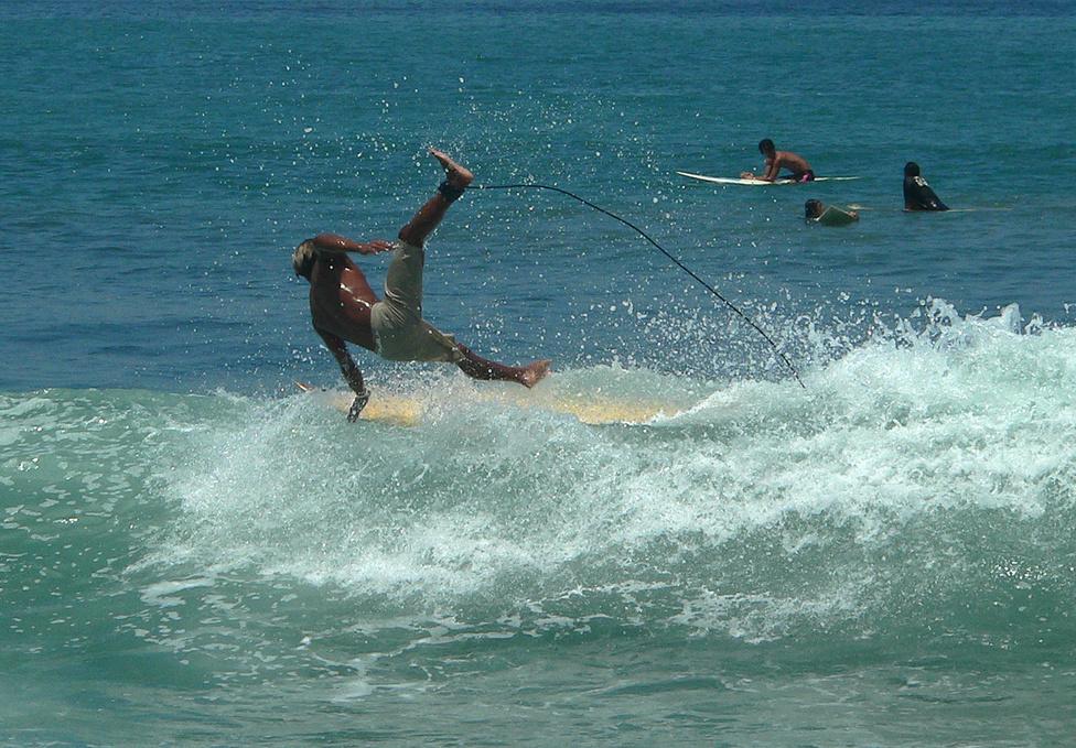 A szorgalmas balinéz nép szigetét tenger veszi körül, ami kikapcsolódásra csábít. Bali strandjai a nagy árapály és az erős hullámzás miatt nem igazán versenyképesek a leghíresebb pancsolószigetek, Mauritius, Dominika, a Maldív-szigetek, vagy Tahiti plázsaival, viszont százszámra vonzzák a szörfösöket. A fotó Kuta Beach központi partszakaszán készült, ahol a relatíve kis hullámokon általában a kezdők gyakorolnak. A parton természetesen megtalálható minden, ami kell: szörfkölcsönzők, szörfoktatók, olcsó kajáldák, ahol újságpapírban adják az ételt, és nejlonzacskóban az italt. A parti út túloldalán persze ott sorakoznak a nemzetközi gyorsbüfé- és kávézóhálózatok üzletei is