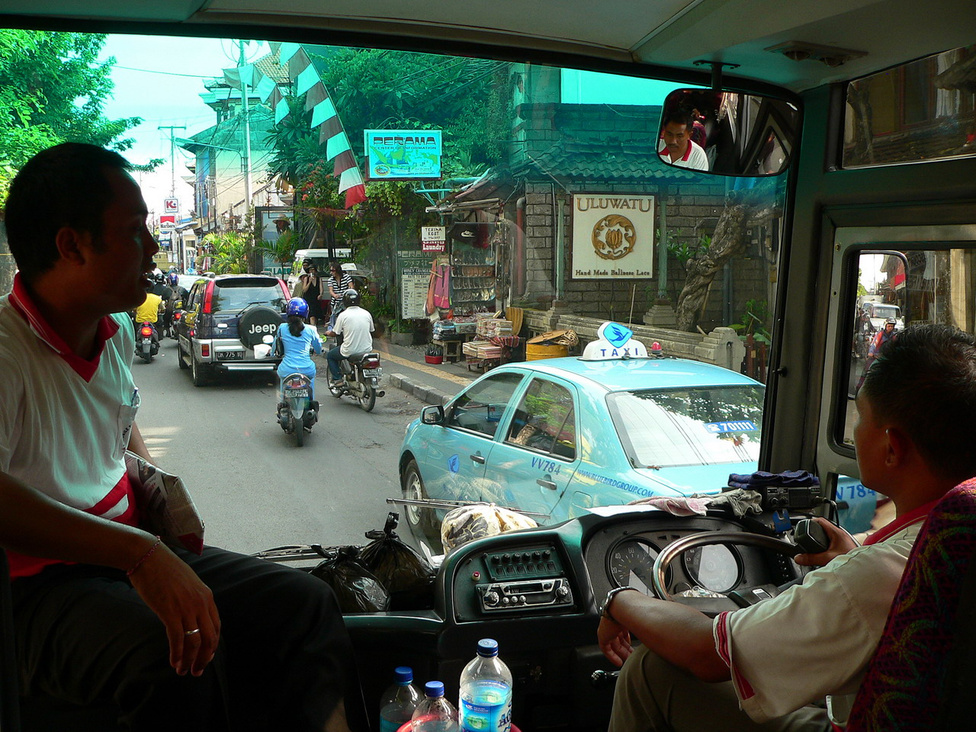 """Az ubudi buszjárat beérkezik Denpasarba. Az épületek földszintjén kézműves ajándékboltok működnek, a keskeny járdán turisták sétálnak, az utcán a forgalom tipikus szereplői közlekednek: robogók, terepjárók, és a sofőr előtt egy Blue Bird taxi. A taxisok Balin is csibészek, a legjobb, ha indulás előtt megegyezünk velük a viteldíjban, aminek reális mértékéről az interneten kereshetünk információkat. A turisták egybehangzó véleménye szerint a Blue Bird a legmegbízhatóbb társaság, korrektül működő taxiórákkal mérik a viteldíjat. Mint a busz műszerfaláról rögtön kiderül, Balin, illetve egész Indonéziában a """"balra tarts!"""" az alapszabály, de nemcsak ezért szokatlan az európaiak számára az ottani közlekedés, hanem azért is, mert a kreszt a sofőrök nagyon kreatívan értelmezik"""
