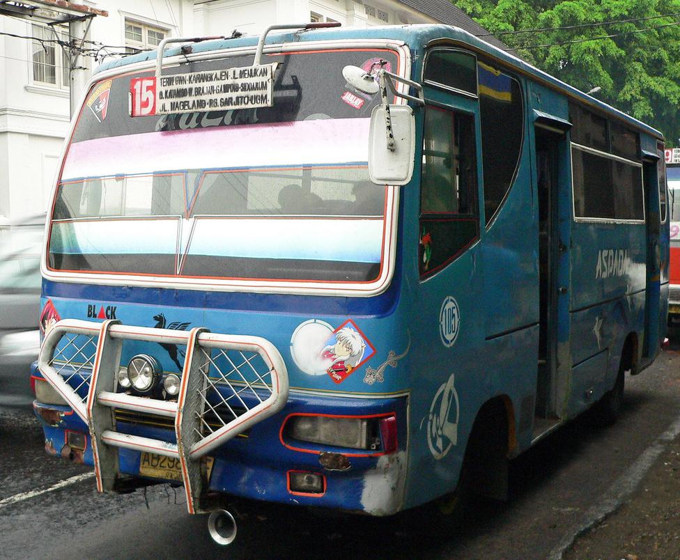 Ez a kisbusz is tanúsítja, hogy a punkság Balin benne van a levegőben – vessük csak össze a látványát mondjuk az egri helyi járatú buszokkal. Na ugye. A nagy első szélvédő fóliázása egyébként elterjedt megoldás a tűző Nap ellen. A sofőr csak a keskeny, fólia nélküli sávban lát ki rendesen, de ez neki elég. Cserébe nem ég szénné a feje műszak végére, ami mindenképpen pozitív fejlemény. Ezeket a buszokat egyébként bemónak nevezik. Nemcsak a megállókban lehet rájuk felszállni, az integető reménybeli utasoknak gyakorlatilag bárhol megállnak