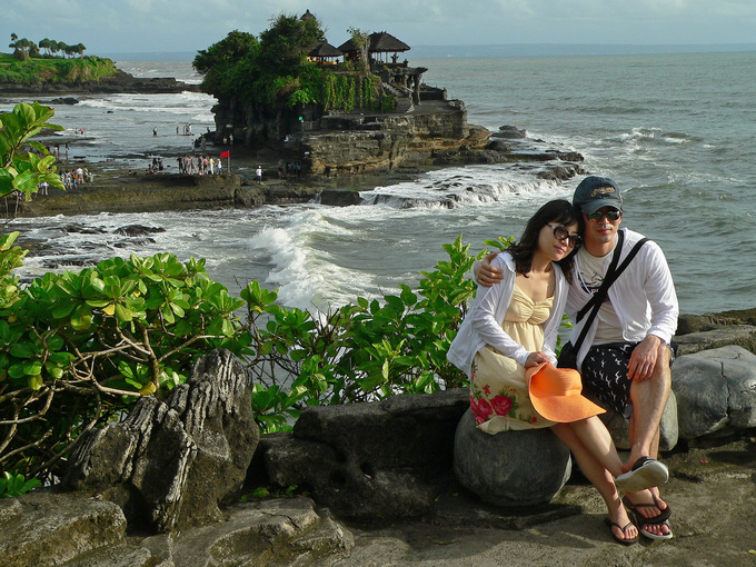 Tourism is now the main source of income for the Balinese. Some come here for a romantic getaway, others are happy just to get some warmth and sunshine in the winter months. The temple of Tanah Lot, located on the Southern shore, is a favourite location among tourists. The area fills up rapidly as the sun sets, with dozens of coaches spewing out passengers armed with cameras. The cliff supporting the temple has been eroded by the sea so much that it had to be reinforced with concrete, shaped to resemble a natural rock formation. This project was financed by the Japanese government which possibly had to do with the fact that Japanese tourists love Bali.