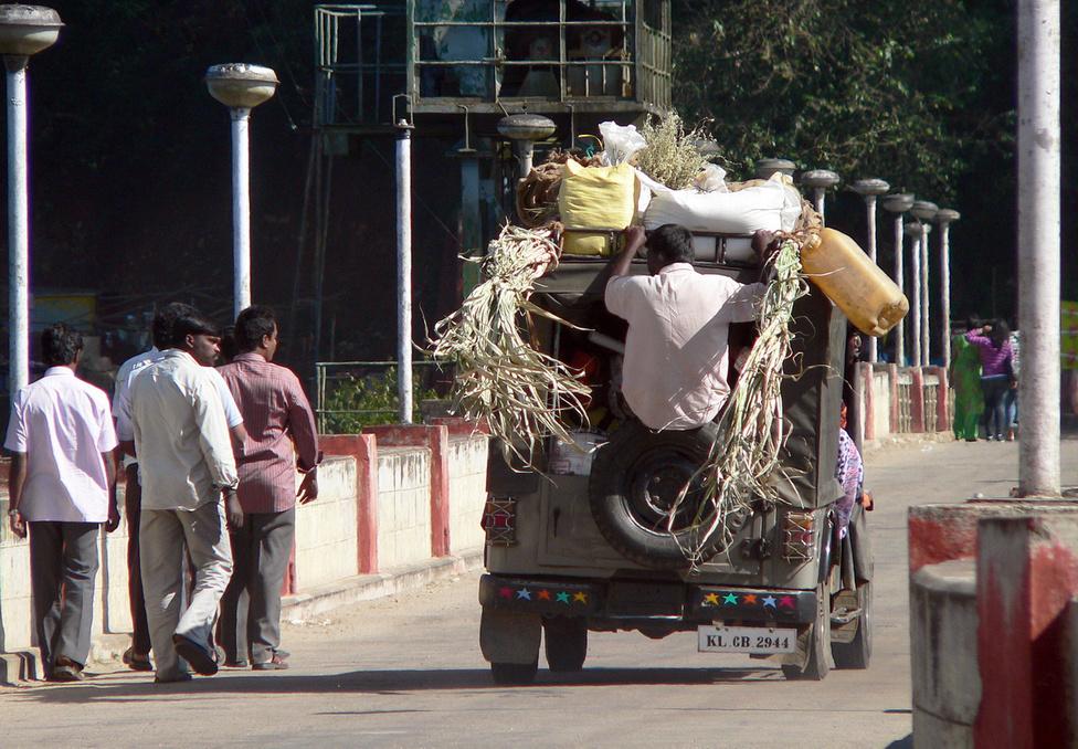 Mahindra rendeltetésszerű használatban Indiában: olyan, hogy túl sok utas vagy túl sok rakomány, nem létezik. Ez a 340-es nemsokára egy meredek szerpentinen fog felkaptatni a Nyugati-Ghát hegységbe. Amikor arra jártam, szerveztünk egy napfelkelte-túrát egy ezer méter körüli csúcsra. A kiindulópontig egy ilyen alap-Mahindrával vittek fel bennünket. Indulás kora hajnalban, vaksötétben, az ablakra vastagon ráfagyva a jég, a dízelolaj megdermedve, a felniken tükörradiál. Miután nagy nehezen elindultunk, a sofőr a fejére húzott vagy öt kötött sapkát, és a szélvédő mellett kihajolva vezetett, miközben mindenki megfagyott mögötte a hátsó padokon. Igazából viszont akkor dermedtünk meg, amikor visszafelé már azt is láttuk, hogy milyen utakon mentünk fel
