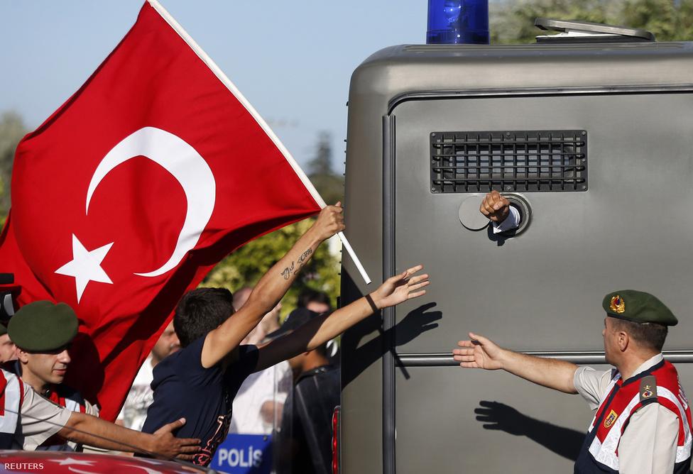 Tüntetők rohannak zászlóval egy rabszállító mögött Törökországban. Augusztusban kezdődtek el a meghallgatások annak a közel háromszáz embernek az ügyében, akiket azzal vádolnak, hogy a kormány megbuktatását tervezték.