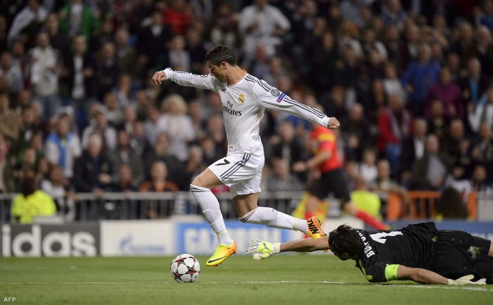 Cristiano Ronaldo tolja el a labdát a vetődő Gianluigi Buffon keze mellett a Bajnokok Ligája csoportkörében rendezett Real Madrid - Juventuson
