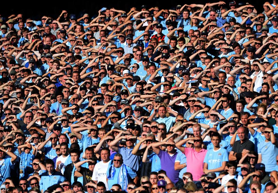 Manchester City szurkolói takarják szemüket a nap elől a United elleni meccsen az Etihad stadionban